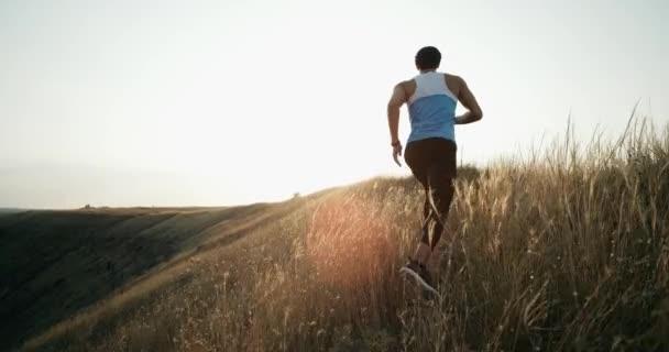 Uomo del corridore corsa jogging al tramonto. Pareggiatore maschio allenamento per maratona corre in salita in siluetta contro il cielo colorato di giallo. Fit fitness modello vivente sano allaperto stile di vita attivo. 4k
