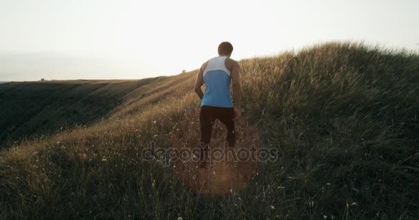 Mužské kondiční výcvik pro Maratonský běh, běh do kopce v siluetě proti barevné žluté oblohy. Přizpůsobit fitness model životní zdravý aktivní venkovní životní styl. 4k