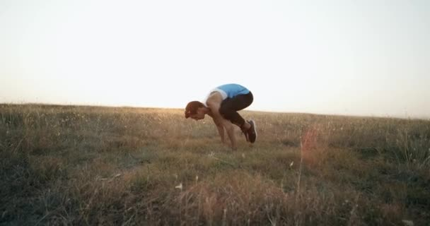 Young sporty man practicing handstand yoga pose at nature. Caucasian guy doing yoga moves and positions outdoors. Beautiful landscape and sky at background. Healthy active lifestyle.