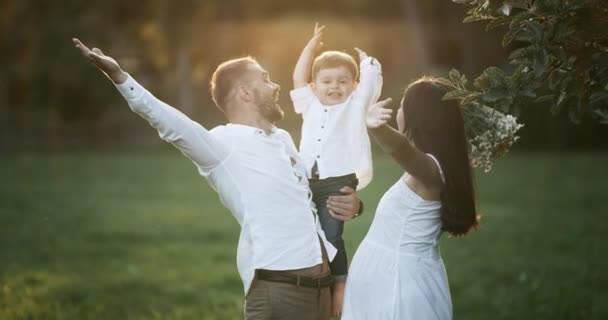 Young family: parents playing with their toddler son. Happy mother and father hugging their baby, smiling outdoors on a sunny day. Happy childhood and parenthood concept.