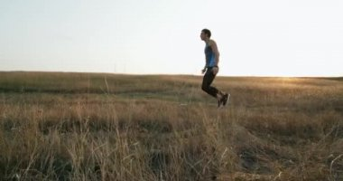 Young male athlet practicing long jumping . Red Epic . Cross country trail run jumping running man.