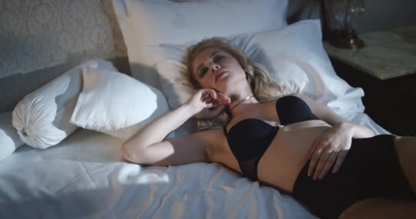 Beauty blonde female with attractive body in sexy lingerie touching her lips and neck. Slow Motion