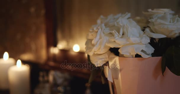 White rose and flickering candles in focus. 4k