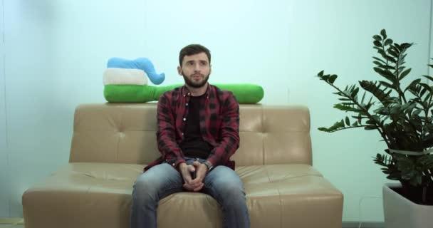 junger Mann sitzt auf dem Sofa und wartet gelangweilt darauf, eingeladen zu werden. Echtzeit