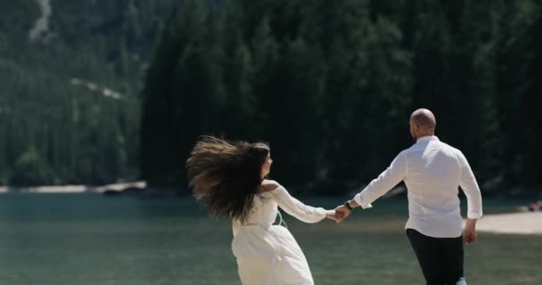 Young man holding the hand of his girlfriend and happy are running down on the shores of a amazing lake.