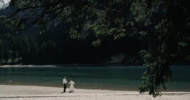 Romantic couple walking in the middle of the forest ,holding the hands, in the background are a amazing lake with mountains. slow motion