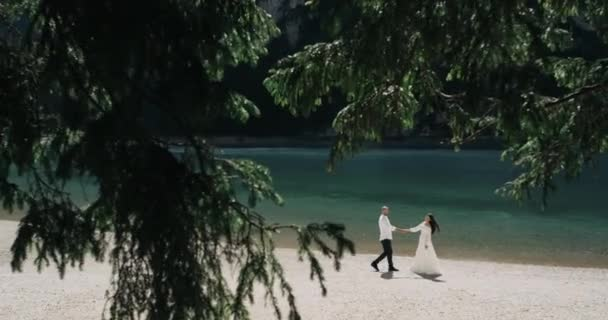 In the middle of the forest with sparkling lake and amazing mountains down to the beach romantic couple walking and holding their hands.