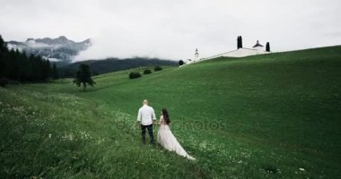 Romantic couple walking around the green field holding the hands and looking at amazing views of forest and mountains