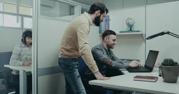 Working day in the office , manager supporting his worker and happy smiling together stand beside the table , background customer support worker sitting on her desk