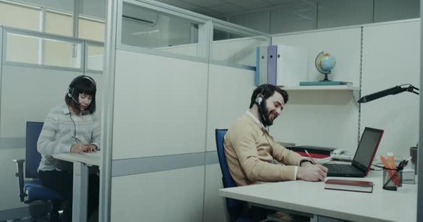 Typický pracovní den ve společnosti centrum zákaznické podpory, pracovník šťastný, mluvit s nimi klient a dávat Ahoj jinému pracovníkovi, který šel za nimi