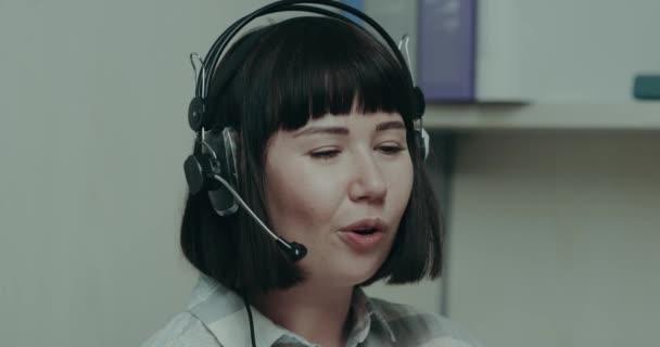 Hezká mladá žena operátor hovoří s klientem v centru volání pomocí sluchátek