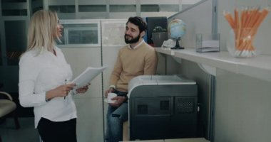 Two office worker woman and men have a conversation , and at the same time female are printing some papers.