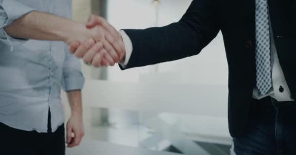V úřadu chodbou dva kolegové drží ruku od sebe.