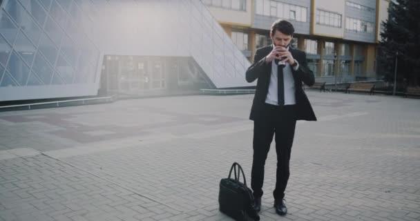 Charismatický obchodní muž v obleku, s ohledem na kávu za obchodní centrum