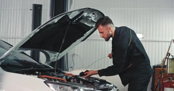 V garáži mechanik muž ve speciální uniformě pečlivě kontrolovat hladinu oleje z auta pak začít opravovat problém