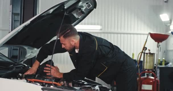 Good looking mechanic guy working on a service auto he fixing the problem of the car in front of the camera he working very concentrated