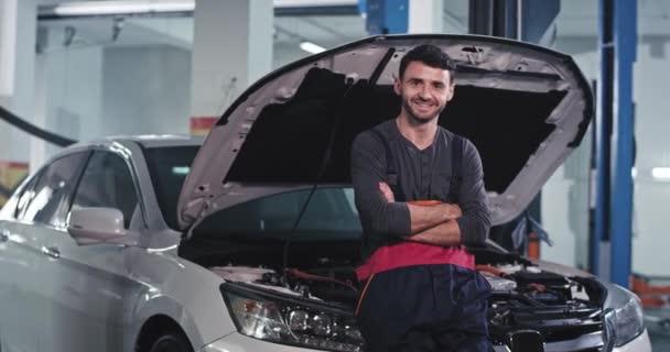 Mechanik v uniformě s velkým úsměvem před kamerou v moderním servisním centru
