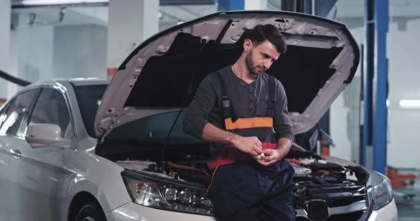 Charismatický mechanik v uniformě stát nad autem a nosit své bezdrátové sluchátka před zahájením práce