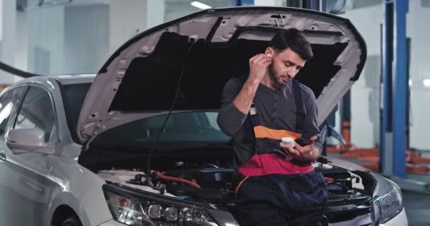 V garáži mechanik chlap velmi atraktivní poslech hudby z jeho bezdrátových sluchátek a podívejte se na jeho telefon, zatímco mají přestávku