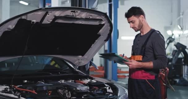 Soustředěný mechanik v uniformě kontrola z mapového seznamu, co je třeba opravit z tohoto auta v autoservisu