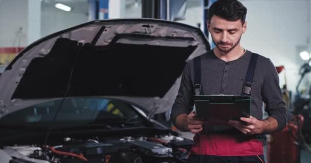 Perfektně vypadající chlap mechanik drží mapu s nějakým seznamem dělat a dívá se přímo do kamery a úsměv velký