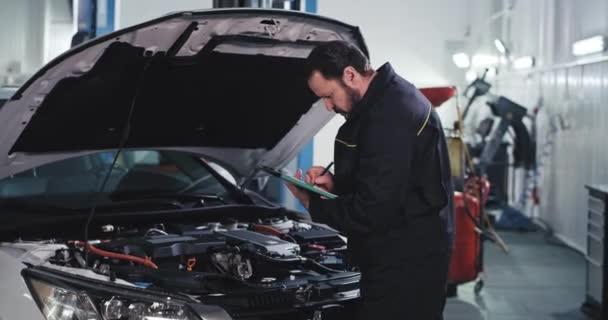 in einer modernen Garage prüfen reife Mechaniker in Uniform einige Dokumente aus der Karte und werfen einen Blick auf das Auto, um zu sehen, was repariert werden muss