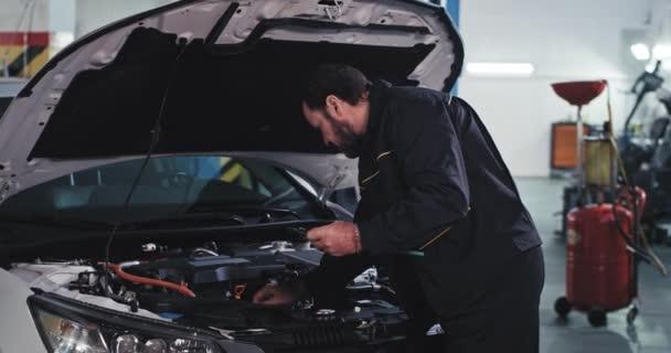 V garáži mechanik se dívá na kameru, opravuje auto a těší se z práce ukazující velký jako na kameru