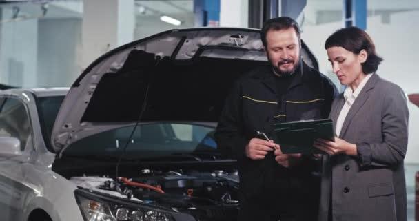 Dobře vypadající mechanik v uniformě a jeho manažerka v obleku si povídají, podívají se z dokumentů a něco podepíší, než začnou pracovat.