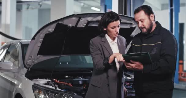 Majitel auta hezká obchodní žena a mechanik chlap analyzující problém vozu z mapy zákazník podepsat nějaké dokumenty v autoservisní středisko a ukazuje velký jako před