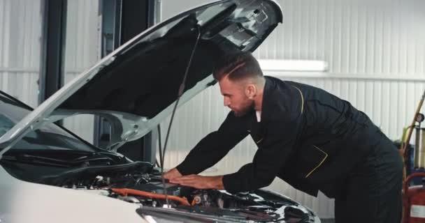 Potící se mechanik v garáži pracuje velmi soustředěný nad autem, opravuje problém, nosí černou speciální uniformu