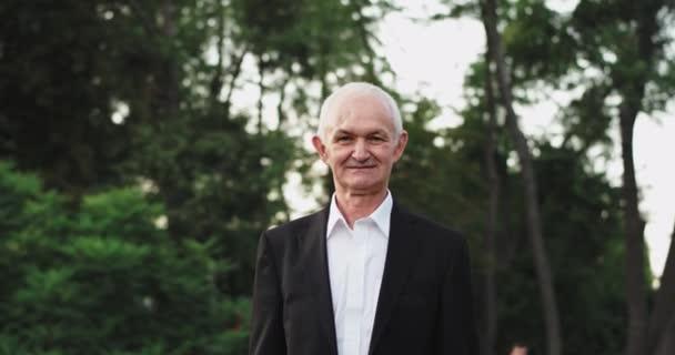 Großvater eines alten Mannes blickt direkt in die Kamera, in einem schwarzen Anzug ein bisschen lächelnd in die Natur