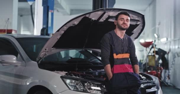 Dobře vypadající chlap před kamerou usměvavý charismatický při opravě auta v auto servisní středisko