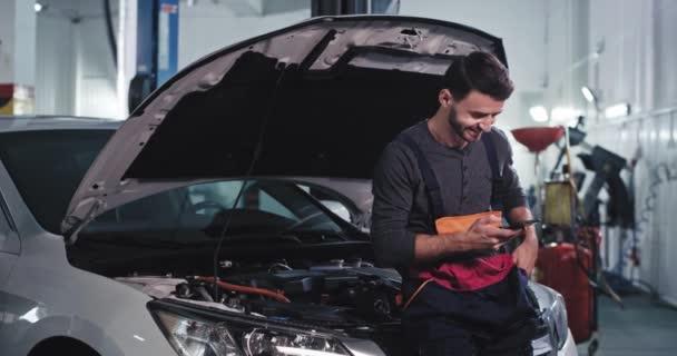 Usmívající se mechanik chlap v uniformě se podívat na jeho telefon při opravě auta v garáži