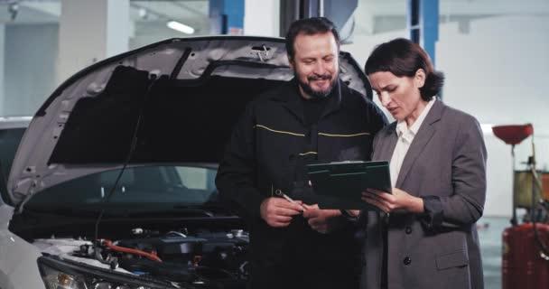 Starší mechanik muž s kancelářským manažerem mít rozhovor v auto servisní středisko mechanik podepsat některé dokumenty před zahájením opravy vozu