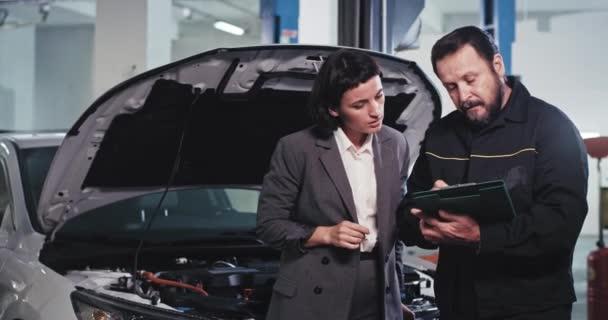 Atraktivní manažerka z kanceláře v autoservisu si popovídá s pracovníkem autoservisu, analyzuje dokumenty a podepíše šťastný, že končí hodně