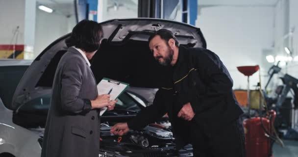 Zákaznice v obleku v servisním autě si popovídají s mechanikem, podívají se přes auto, aby zjistili, kde je problém opravit