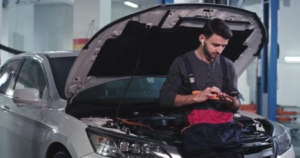 Atraktivní mechanik v uniformě mít přestávku zkontrolovat jeho telefon sedí vedle auta, mají skvělou náladu a šťastný obličej