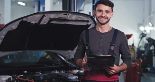 Good looking man mechanic smiling large in front of the camera showing a big like while working on a car in a modern auto service center