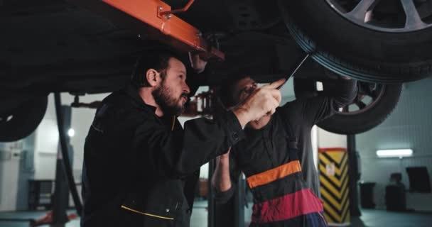 Charismatický dospělý muž mechanik a jeho pomoc v moderní auto servis pod poškozeným autem pomocí baterky se snaží najít problém opravit, že