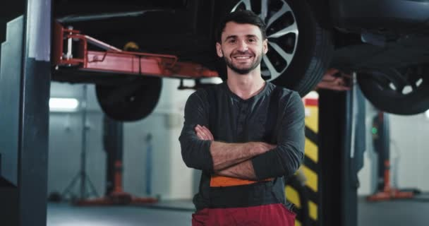 Portrét před kamerou usměvavý velký mechanik v moderním servisním středisku si odskočil přímo do kamery