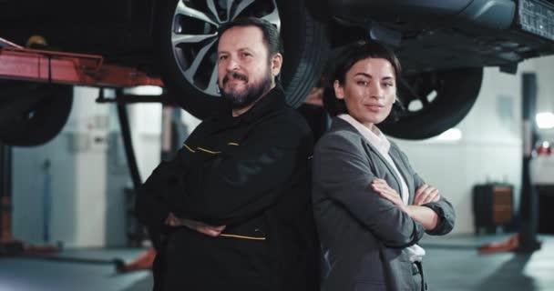 vor der Kamera die schöne Dame im Anzug Geschäftsfrau und der Automechaniker, die direkt in die Kamera schauen sie sind in einem modernen Auto-Service-Center