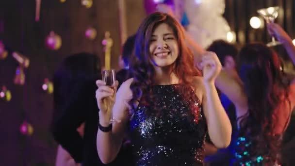 Charismatická usměvavá mladá žena se sklenicí šampaňského před kamerou na večírku, užívající si večer. Zastřelen na Arri Alexa Mini