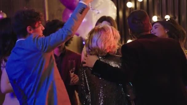 Okouzlující velký večírek mladí lidé těší večer na sobě ležérní a šumivé oblečení tanec a pocit vzrušení