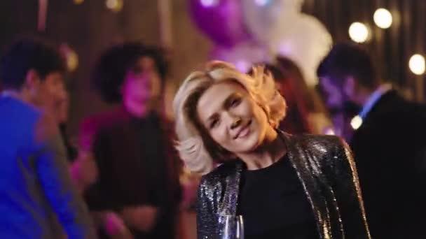 attraktive heiße blonde Dame in silber glitzerndem Sakko vor der Kamera mit einem Glas Champagner und genießt die Zeit bei glamourösen Party-Abenden