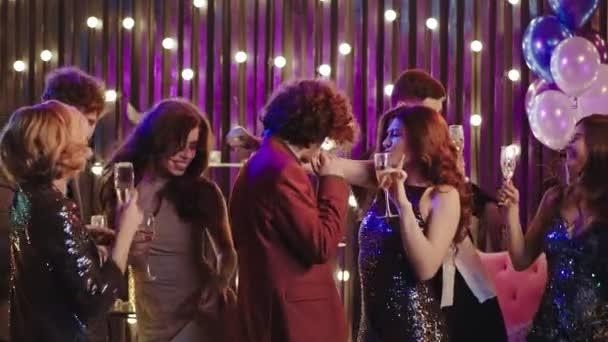 Mosolygó nagy baráti társaság a születésnapi partin élvezik, hogy este pezsgőt isznak menő ruhákban.