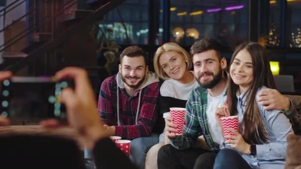 glücklich und lächelnd Gruppe von Freunden sehr charismatisch sitzt auf einem großen Sofa hält in einer Gruppe anderen Freund Fotos für Erinnerungen an sie