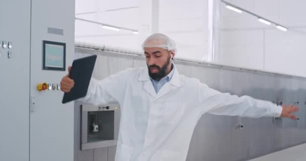 In a big manufacturing industry engineer man with a beard walking beside of industrial machine holding a tablet and moving funny he start to checking the machine , walking on the background other