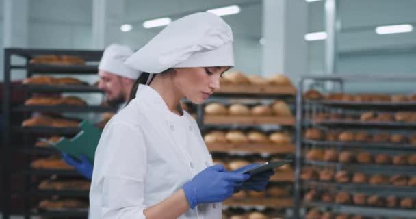 Csinos fiatal hölgy pék csinál néhány képet a tablettával egy friss sült kenyeret a polcokról aztán megnézi a képeket, fehér egyenruhát visel kalapban a pékségben.