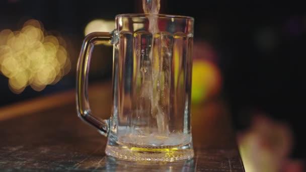 Közelkép a kamera egy lassított felvételű hideg sör öntött egy pohár sört, hogy buborékok
