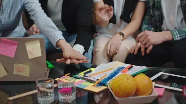 Power Team Gruppe von Büroangestellten sehr charismatisch Hände zusammenlegen und glücklich zusammen arbeiten, während sie auf dem Sofa sitzen